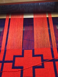Here I have raised half of the purple threads. The selected orange threads stay above while I weave with purple thread.
