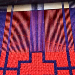 I have raised the half of the orange threads and the selected purple threads stay up while I weave with orange.